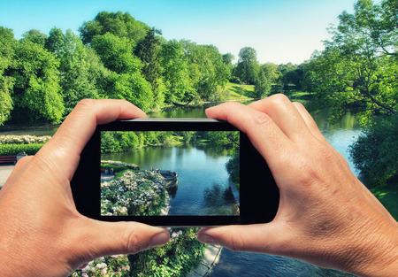 Man and woman hand capturing beautiful city park with smartphone. photo