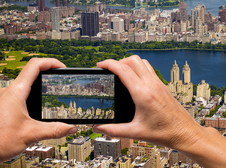 Man and woman hand capturing New York aerial skyline with smartphone photo