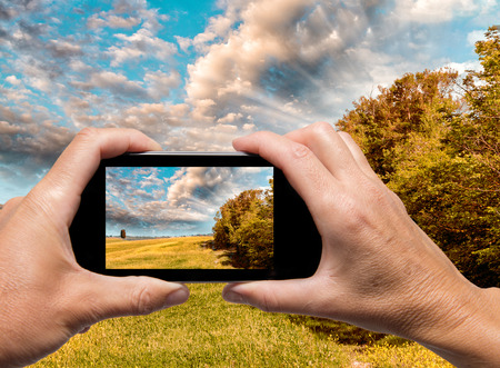 Man and woman hand capturing Tuscany spring landscape with smartphone. photo