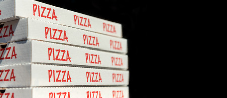 Large stack of pizza boxes. Isolated over black. Stock Photo