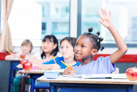 multi race: Chica afroamericana que levanta la mano en un aula raza m�ltiples.