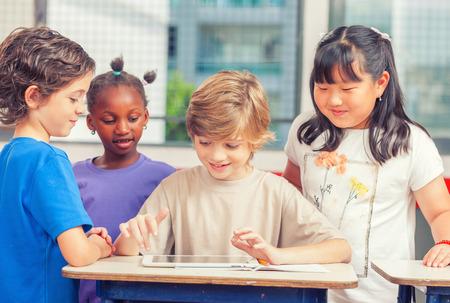 다문화 교실 태블릿 학교에서 함께 연주입니다. 행복과 공생 개념입니다. 스톡 콘텐츠