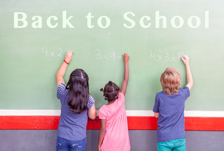 multi race: Back to school. Primary multi race classroom writing on chalkboard. Stock Photo