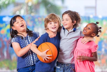 niños sentados: Niños felices que abrazan mientras jugaba al baloncesto. Unión concepto de la escuela primaria. Foto de archivo