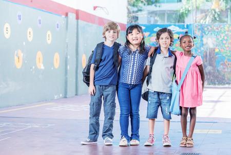 multi racial: Schoolchildren embracing happy. Multi cultural racial classroom.