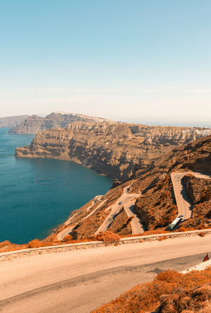 paved: A paved road curving down a hillside towards the ocean