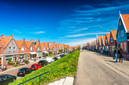 volendam: VOLENDAM, NETHERLANDS - APRIL 27, 2015: Classic homes aligned along city street. Volendam is a famous tourist attraction. Editorial