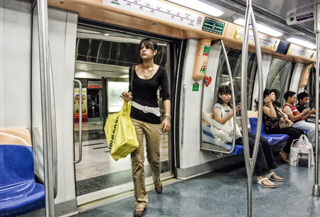SINGAPORE - JULY 12, 2008: People on the subway. Underground system serves more than 2 million people daily. Editorial