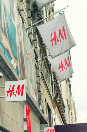hm: NEW YORK CITY - JUNE 14, 2013: Modern H&M shop entrance and flags in 5th street, New York City. Editorial