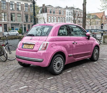 subdivision: LEIDA, NETHERLANDS - APRIL 26, 2015: Fiat 500 in pink color along city canal. Fiat is a subdivision group of great autumobiles group FCA.