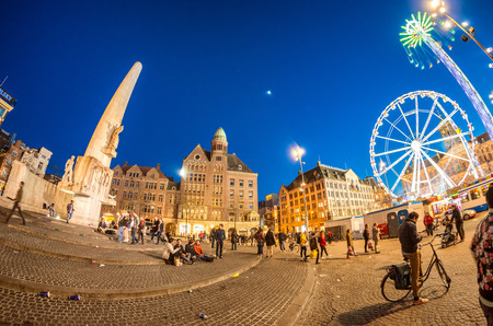 dam square: AMSTERDAM - APRIL 25, 2015: Tourists and locals in Dam Square at night. The city attracts almost 10 million people annually.