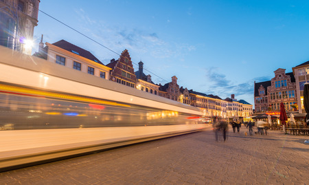 GENT, BELGIUM - APRIL 20, 2015: Tram moves fast in city center. Gent is a busy city which hosts many students and tourists spending the night outside.