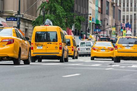 populate: NEW YORK CITY - JUNE 13, 2013: Yellow cabs along Manhattan avenue. More than 13,000 taxis populate the city.
