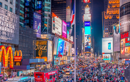 NEW YORK CITY - JUNE 8, 2013: Tourists in Times Square at night. More than 50 million people visit New York every year. Editorial