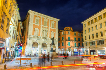 annually: PISA, ITALY - MAY 24, 2014: Tourists in Garibaldi Square at night. The city attracts 3 million people annually.