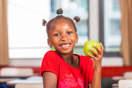 niños negros: niña africana en la escuela que sostiene la fruta verde manzana. Foto de archivo