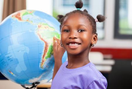 アフリカの女の子が学校で地球儀に触れます。