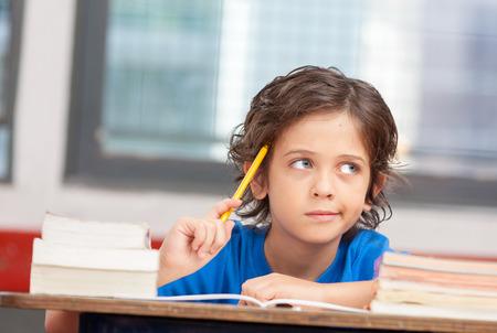 ni�os pensando: Muchacho joven en la escuela pensando en la soluci�n del problema. Concepto de inspiraci�n.