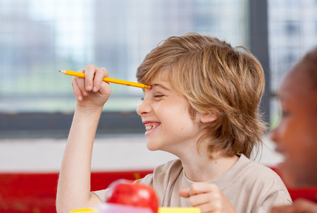 smart boy: Happy young boy at school smiling holding pencil with right hand. Stock Photo