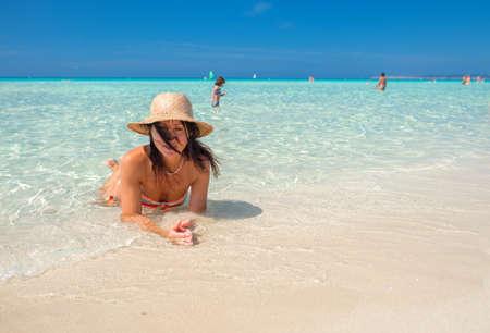 monokini: Beautiful woman laying down in the tropical water. Stock Photo