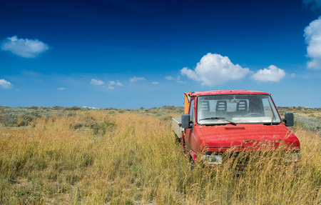 the passing of time: Abandoned red truck in the middle of a yellow meadow against blue sky. Passing time concept. Stock Photo