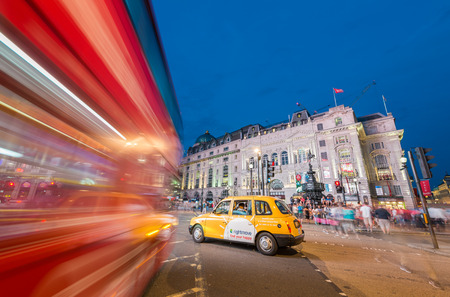 piccadilly: LONDON - JUNE 15, 2015: Buses and traffic in Piccadilly Circus at night. London attracts 50 million people across the world.