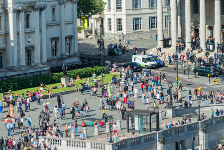 annually: LONDON - JUNE 12, 2015: Tourists in Trafalgar Square. London attracts 50 million people annually.