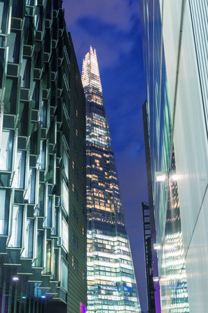 shard: LONDON - JUNE 12, 2015: The Shard at night framed by buildings. The Shard, standing 309m, is the tallest building in Europe