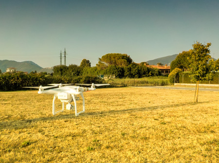 Drone hovering over countryside landscape.