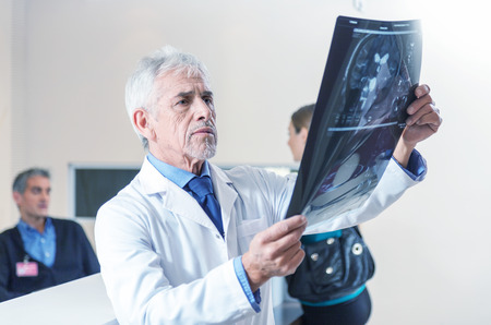 Expert doctor analyzing x-ray scan at hospital.
