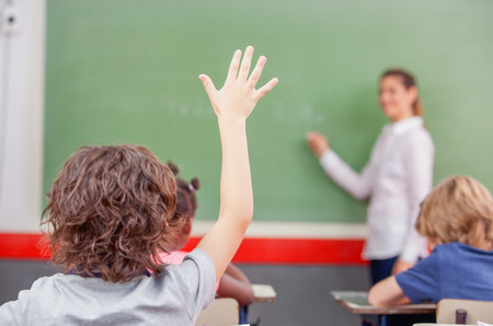 Education, elementary school, learning and people concept - group of school kids with teacher sitting in classroom and raising hand. Stok Fotoğraf - 43936277