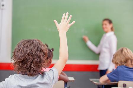 Výchova, základní škola, učení a koncept lidí - skupina školních dětí s učitelem sedí ve třídě a zvyšuje ruku.