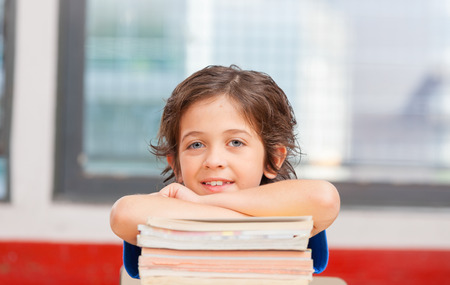 successfull: Kid resting on the books in his classroom. Happy school concept. Stock Photo