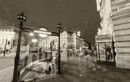 piccadilly: LONDON - JUNE 11, 2015: Black and white vintage traffic scene near Piccadilly Circus. The city attracts 50 million people annually.