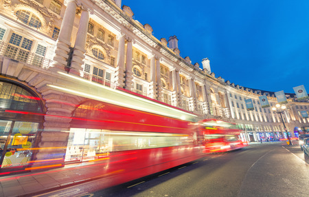 regent: LONDON - JUNE 11, 2015: Night traffic and tourists in Regent Street. London is visited by 50 million people annually.