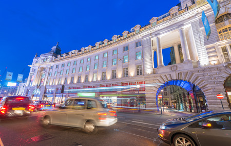 annually: LONDON - JUNE 11, 2015: Night traffic and tourists in Regent Street. London is visited by 50 million people annually.