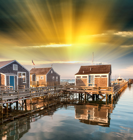 cape cod style: Beautiful homes of Nantucket, Massachusetts. Houses over water at dusk.