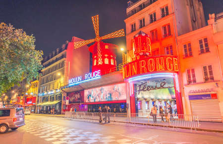 locating: PARIS - JUNE 9: The Moulin Rouge by night, on June 9, 2014 in Paris, France. Moulin Rouge is a famous cabaret built in 1889, locating in the Paris red-light district of Pigalle.