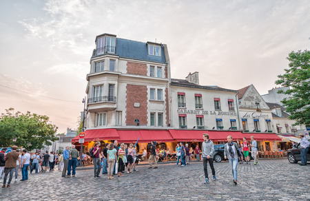 preferred: PARIS - JUNE 12, 2014: Tourists in Montmartre in the evening. Montmartre is one of the preferred attractions in Paris Editorial