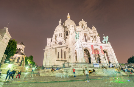 annually: PARIS - JUNE 12, 2014: Tourists along Montmartre Hill. Paris is visited by 30 million people annually. Editorial
