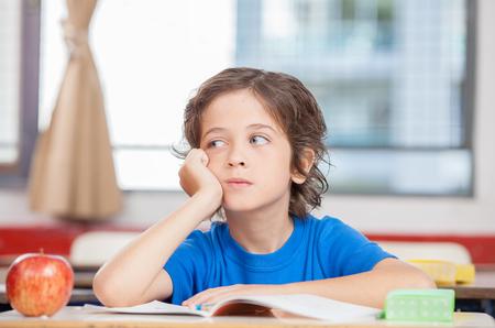 niños en la escuela: Pensando niño en el aula. Foto de archivo
