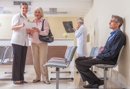 pacientes: Los médicos y los pacientes en la sala de espera del hospital.