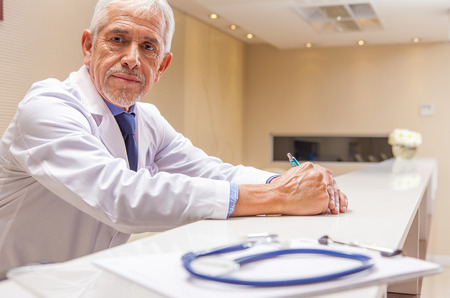 malpractice: Worried expert male doctor expression with stethoscope in foreground. Stock Photo