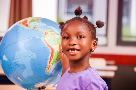 geography: African schoolgirl learning geography with world globe. Stock Photo