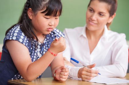 asian teacher: Asian kid at school learning math with teacher. Stock Photo