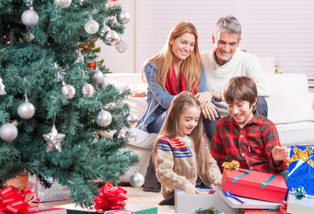 Christmas family concept. Adults and children exchanging gifts.