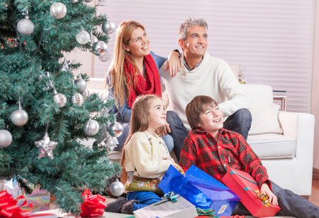 Happy family exchanging gifts for Christmas. Stock Photo