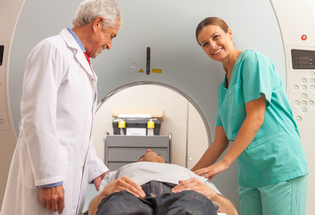 x ray equipment: Patient undergoing mri scan assisted by doctors. Hospital and health concept. Stock Photo