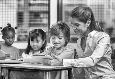 multi ethnic children: Group of multi ethnic children studying in elementary classroom.
