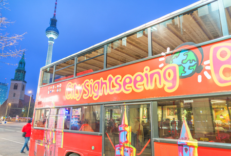 than: BERLIN - NOVEMBER 15, 2013: City sightseeing bus at night. Berlin attracts more than 10 million people annually.